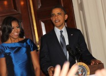 First Lady Michelle Obama and President Obama welcome guests at a White House holiday party