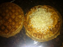 Waffles with crunchy peanut butter and a sprinkle of sesame seeds.